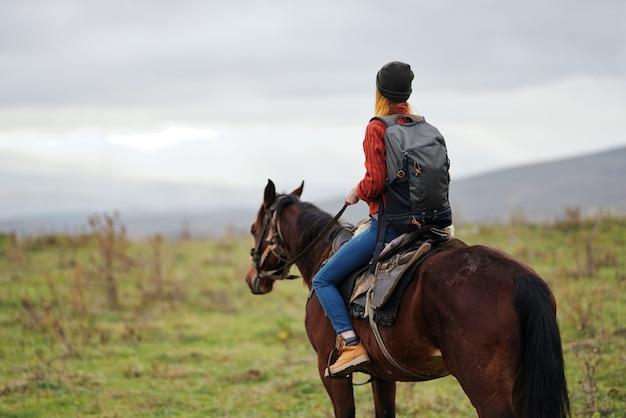 Vrouw wandelaar met rugzak rijden paard reizen vrijheid