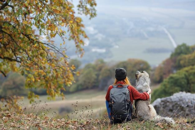 Vrouw wandelaar naast hond bewondert natuur bergen reizen