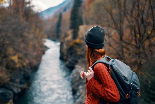 Vrouw wandelaar rugzak rivier reizen naar de bergen