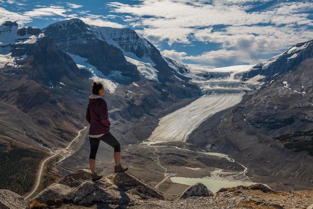 Vrouw wandelaar staande op wilcox piek uitkijkend over de columbia icefields en de athabasca gletsjer, in jasper, alberta, canada