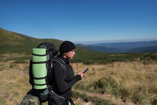 Vrouw wandelaar staat op de top van de berg, houdt de telefoon in haar handen en typt een bericht