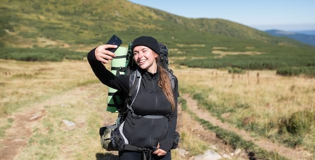 Vrouw wandelaar staat op de top van de berg, houdt een telefoon in haar handen en neemt een selfie op haar smartphone