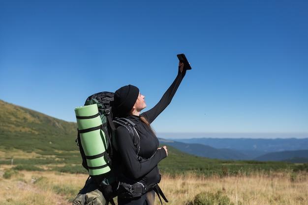 Vrouw wandelaar staat op de top van de berg, houdt een telefoon in haar handen en voert een videogesprek