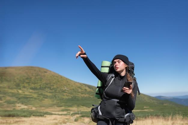 Vrouw wandelaar staat op de top van de berg, wijsvinger van haar hand wijst