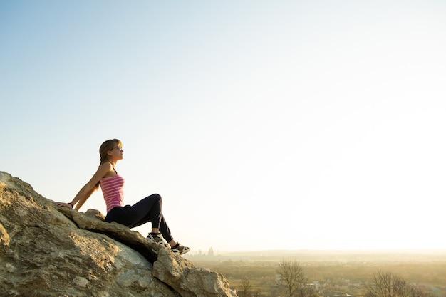 Vrouw wandelaar zittend op een steile grote rots genieten van warme zomerdag. jonge vrouwelijke klimmer rust tijdens sportactiviteiten in de natuur. actieve recreatie in de natuur concept.