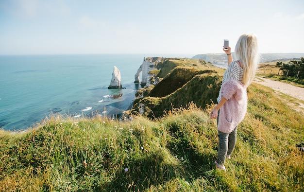 Vrouw wandelen en het nemen van foto van etretat kliffen en de atlantische oceaan in etretat, frankrijk