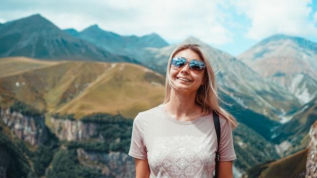 Vrouw wandelen in de bergen op zonnige dag. uitzicht op kazbegi, georgië