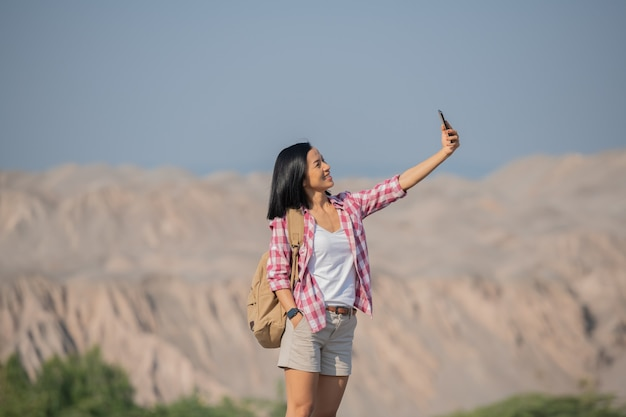 Vrouw wandelen in de bergen staande op rotsachtige topkam met rugzak en paal uitkijken over landschap, gelukkig vrouw zelfportret maken in de bergen