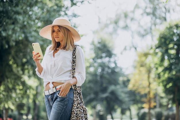Vrouw wandelen in het park en praten over de telefoon