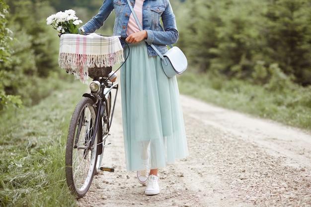 Vrouw wandelen met fiets in bos