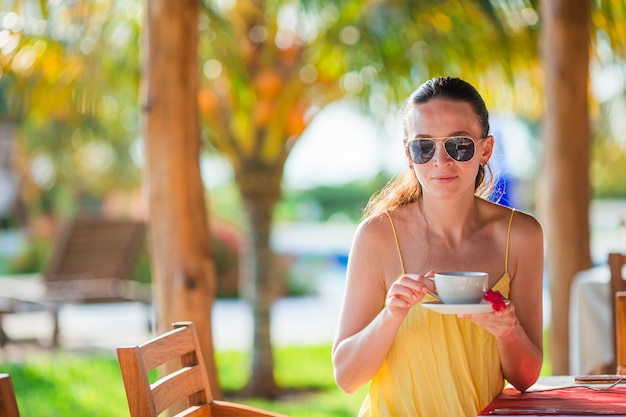 Vrouw warme koffie drinken op luxe hotelterras met uitzicht op zee in het resort restaurant.