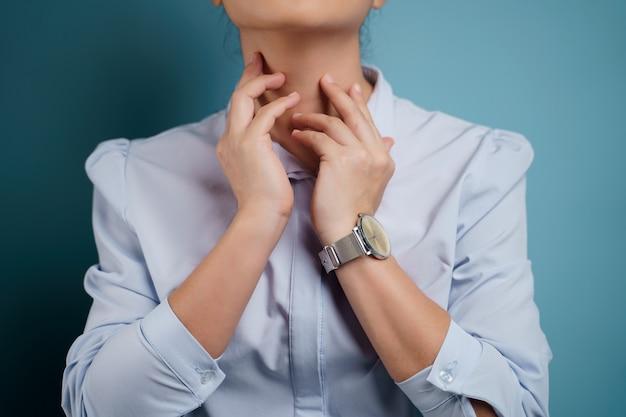 Vrouw was ziek met zere keel geïsoleerd op blauw.
