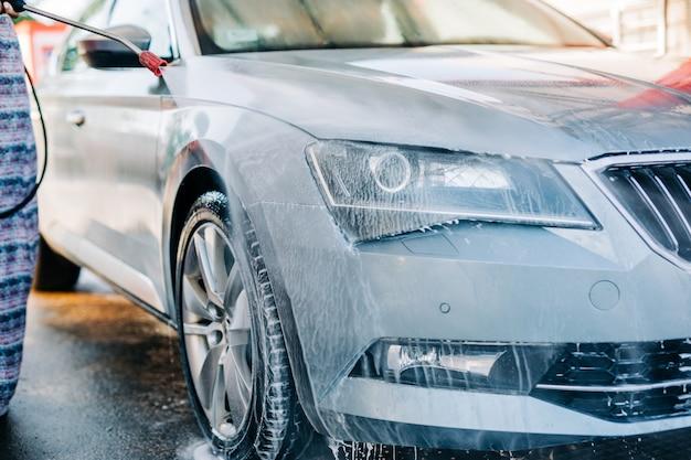 Vrouw wassen auto bij autowasstation met behulp van hogedruk watermachine.