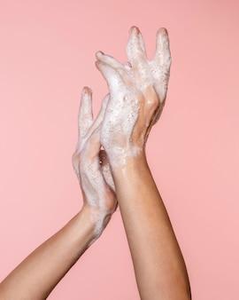 Vrouw wassen handen geïsoleerd op roze
