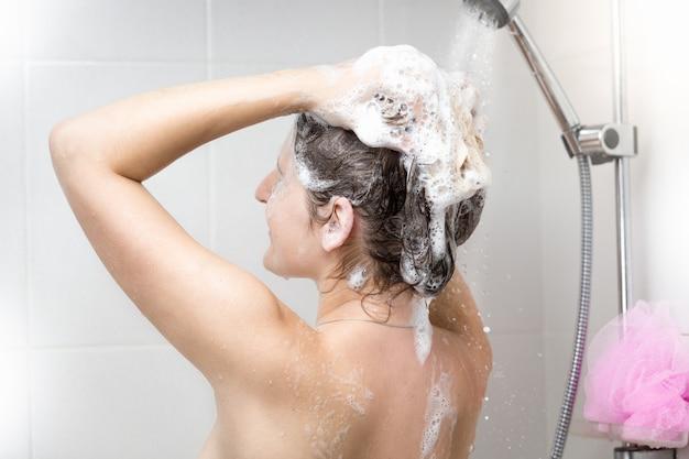 Vrouw wassen hoofd met shampoo in douche