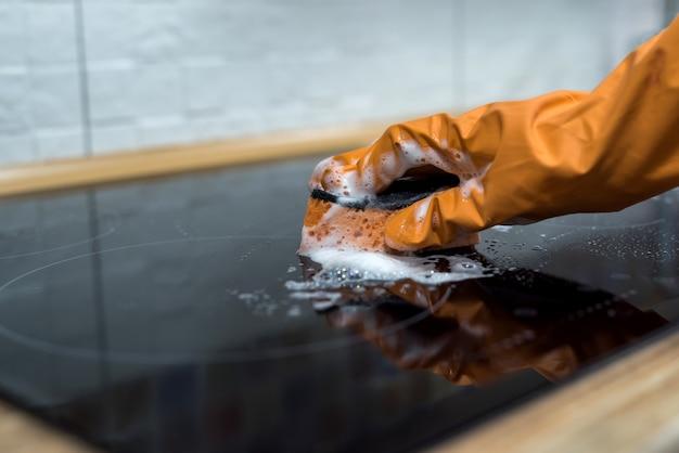 Vrouw wassen moderne kookplaat koken paneel in de keuken. schoon