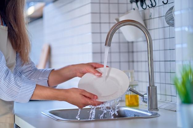 Vrouw wassen plaat in witte moderne keuken close-up