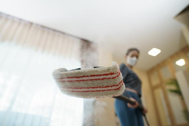 Vrouw wast de vloer met een stoommop.