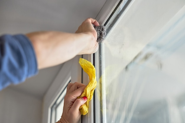 Vrouw wast een glas wit plastic raam