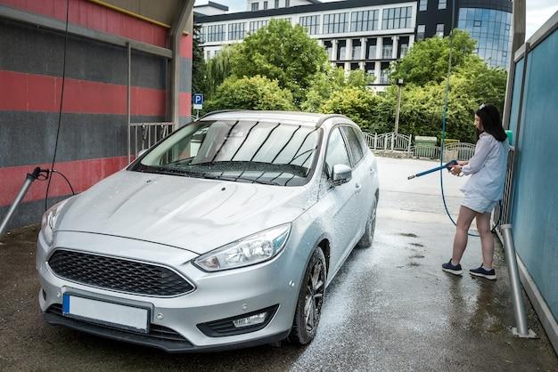 Vrouw wast haar auto met waterpistool en wast het schuim af. automatische schoonmaak