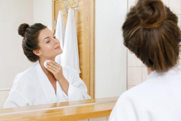 Vrouw wast haar gezicht met lotion en wattenschijfjes