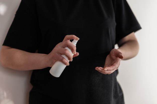 Vrouw wast haar handen met een antiseptische spray tegen ziektekiemen, virussen en bacteriën. bescherming tegen coronavirus