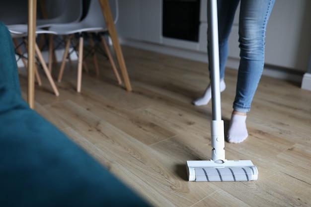 Vrouw wast vloer met dweildiensten van schoonmaakbedrijven