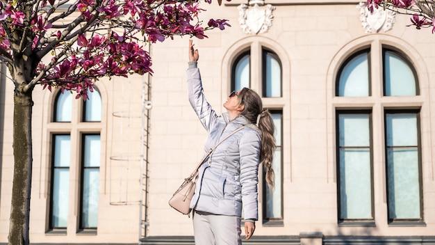 Vrouw wat betreft boom met roze bloemen. oud paleis gemaakt in klassieke europese stijl op de achtergrond