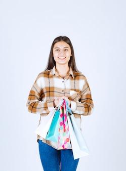 Vrouw weergegeven: stelletje boodschappentassen over witte muur.