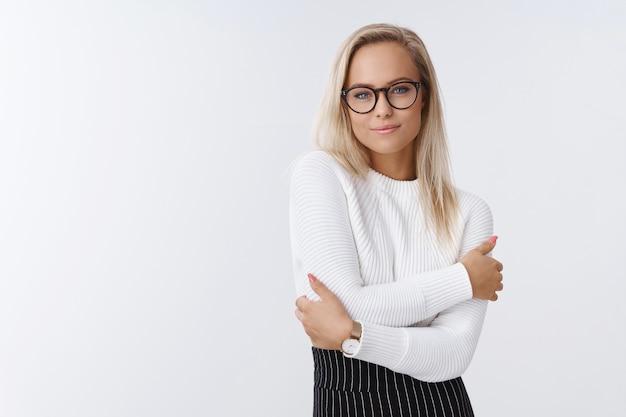 Vrouw weet hoe elegant en warm aankleden in de winter op kantoor op een witte achtergrond in trendy trui en bril knuffelt, zichzelf knuffelt en zich gezellig en comfortabel voelt glimlachend zacht.