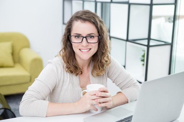 Vrouw werken met laptop en drinkende thee thuis