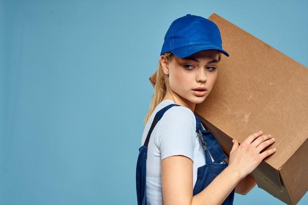 Vrouw werkende formulier doos in handen verpakking bezorgservice blauwe muur.