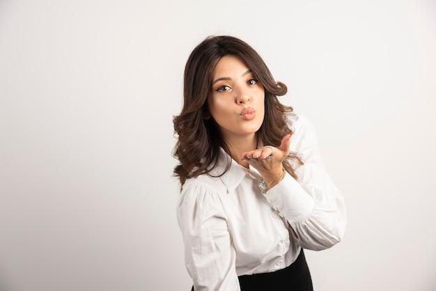 Vrouw werknemer blaast kus op wit.
