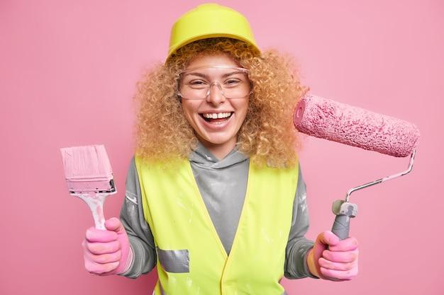 Vrouw werknemer draagt beschermende helm glimlacht graag bouwgereedschap vast omdat professionele bouwer probeert het werk op tijd af te maken gekleed in uniform