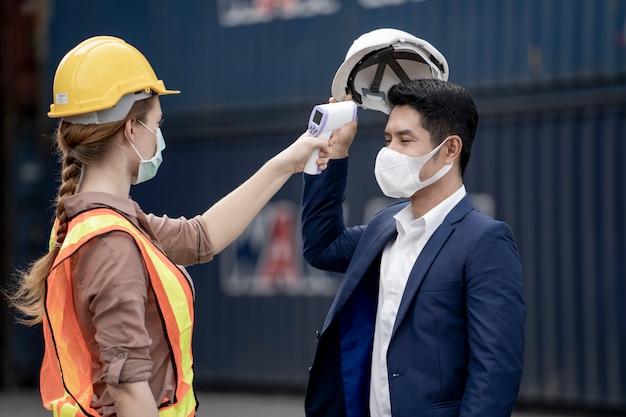 Vrouw werknemer in een gezicht medisch masker en veiligheidskleding gebruikt meet temperatuur bij werknemers mensen.