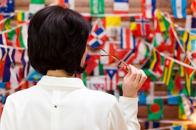 Vrouw werknemer in een witte blouse met bril in de hand staat voor vlaggen, uitzicht vanaf de achterkant.