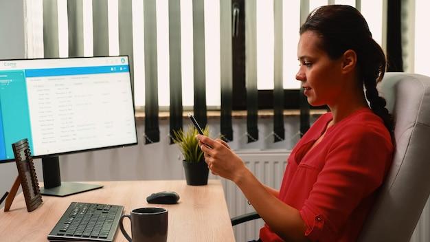 Vrouw werknemer schrijven op mobiele telefoon voor computer in kantoorruimte. spaanse ondernemer zit op de werkplek van een bedrijf en neemt pauze terwijl hij op een smartphone typt voor de pc die nieuws leest