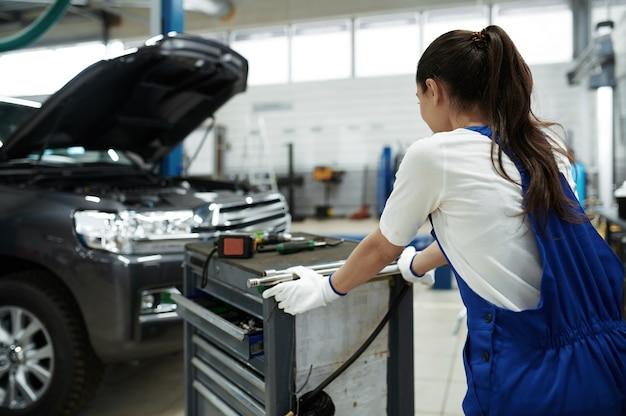 Vrouw werknemer staat op de motorkap in mechanische werkplaats
