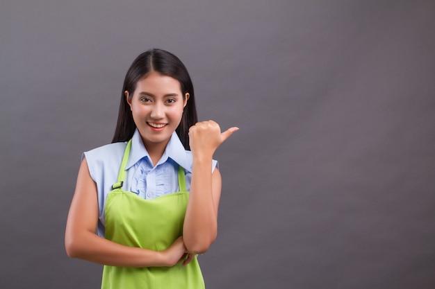 Vrouw werknemer wijzende duim omhoog, iets presenteren op lege ruimte