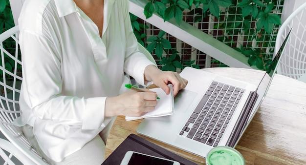 Vrouw werkplek cafe terassa freelancer pc laptop zomer wit