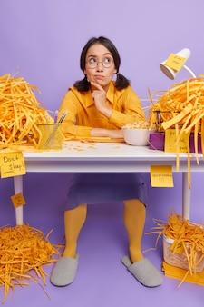 Vrouw werkt aan bureau geconcentreerd boven denkt aan het maken van een nieuw project heeft puinhoop in de kast na het snijden van papier op paars