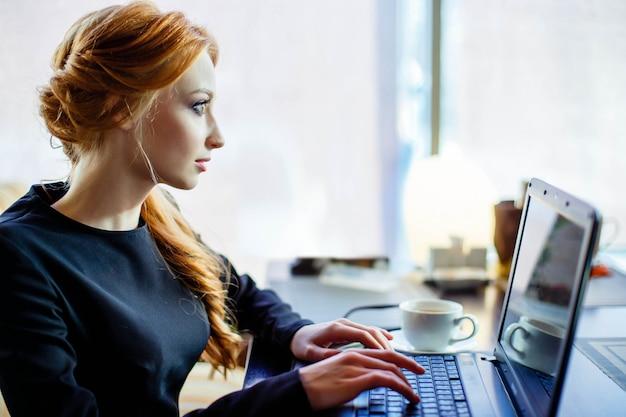 Vrouw werkt aan de laptop in het café