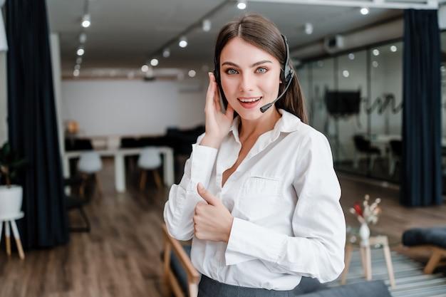 Vrouw werkt als call center ondersteuning exploitant met hoofdtelefoon duimen opdagen en glimlachen