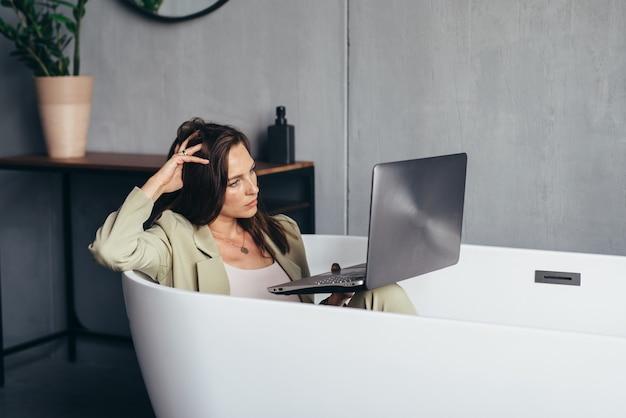 Vrouw werkt in de badkuip met haar laptop in de privacy van haar huis.