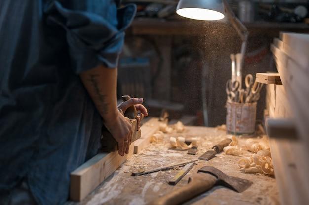 Vrouw werkt in een werkplaats met een bos. tool schrijnwerker