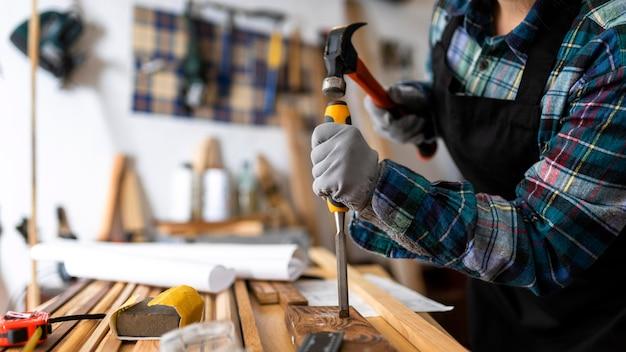 Vrouw werkt in werkplaats met hout