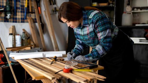 Vrouw werkt in werkplaats met meetlint