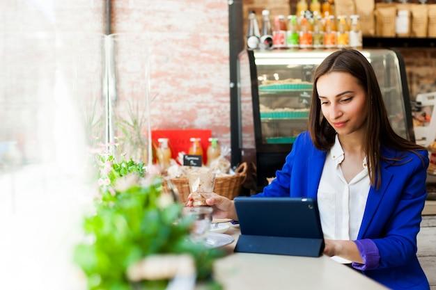 Vrouw werkt met een tablet aan de tafel in een cafe