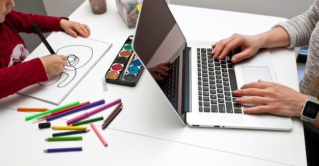 Vrouw werkt met laptop terwijl haar zoon schilderen in de keuken