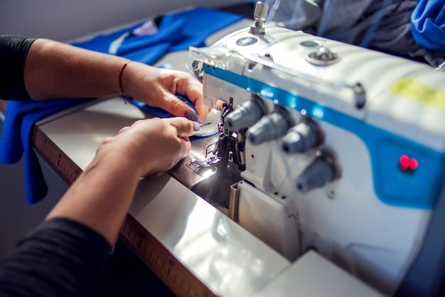 Vrouw werkt met naaimachine. vervaardiging van draagconcept